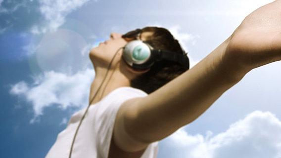 Junge mit Kopfhörern genießt die Musik unter blauem Himmel. © Alexey Klementiev - Fotolia
