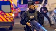Das Bild zeigt einen bewaffneten Polizisten während des Großeinsatzes vom 13. November 2015. © dpa Bildfunk Fotograf: Ian Langsdon