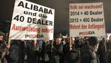 """Pegida-Demonstranten halten ein Plakat hoch mit der Aufschrift: """"Alibaba und die 40 Dealer. Ausweisung sofort!"""" © epd-bild Fotograf: Matthias Schumann"""