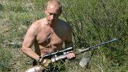 Wladimir Putin streift mit Gewehr und nacktem Oberkörper durch Flora und Fauna. © dpa - Report
