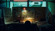 Zu sehen ist ein dunkler Raum, in dem Recherche-Material hängt. © STRG_F / ARD