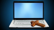 Ein Holzkreuz liegt auf einem Laptop © Fotolia Foto: Kovac, vectomart, Maksym Yemelyanov