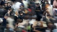 Menschenmassen drängeln sich über eine Haupstraße in Tokio - verfremdet. © dpa - Bildfunk