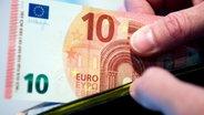 Eine Hand zieht eine neue 10-Euro-Banknote aus einem Portemonnaie. © dpa - Bildfunk Fotograf: Boris Roessler