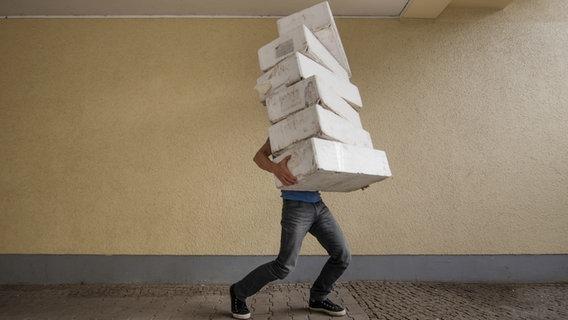Das Bild zeigt einen Menschen, der einen Stapel Pakete trägt. ©  kallejipp / photocase.de