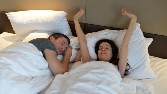 Eine Frau liegt im Bett und streckt sich, neben ihr schläft ein Mann. © picture alliance / dpa Themendienst