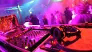 Eine Disco aus der Sicht des DJ-Pultes: Im Vordergrund liegen Kopfhörer auf dem Pult, im Hintergrund tanzen Menschen. © dpa