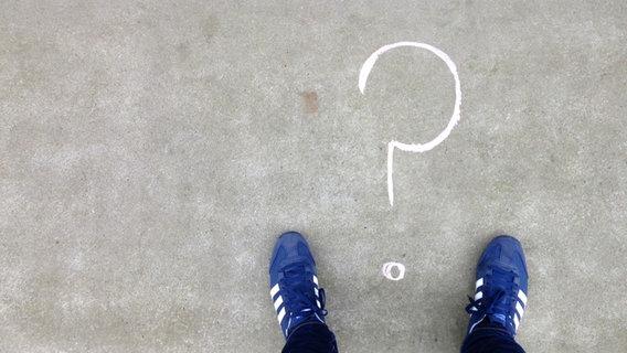 Ein auf ein Stein gemaltes Fragezeichen wir dvon zwei Sneakern flankiert. © NDR Foto: Pascal Strehler