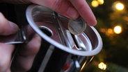 Eine Frau steckt ein Geldstück in eine Spendenbüchse © picture alliance / dpa Themendienst