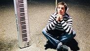 Ein Junge sitzt auf dem Boden neben einem Keyboard. © Photocase Fotograf: Prinzip