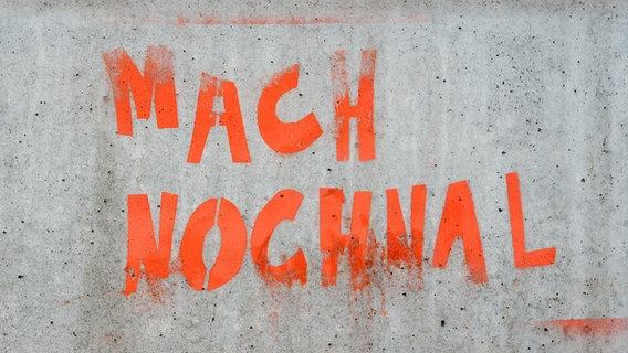 """""""Mach nochmal"""" steht auf einer Wand in orangener Neonfarbe. © Photocase Foto: Soer Alex"""