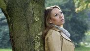 Frau lehnt an Baum © picture-alliance