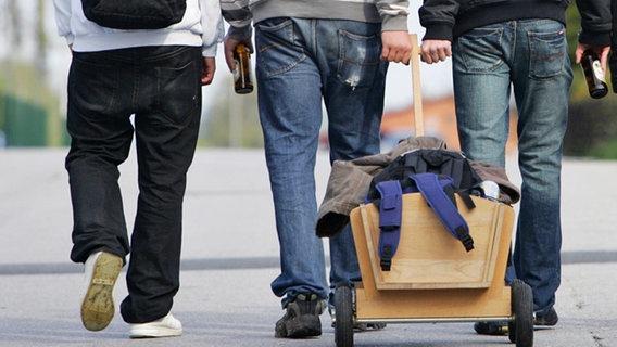 Männer, die einen Bollerwagen am Vatertag hinter sich herziehen © dpa - Report