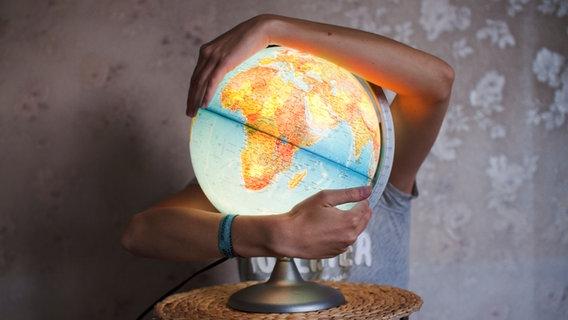 Ein Junge umarmt eine leuchtende Weltkugel. © Photocase Foto: Sick Rick
