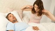 Frau hält sich die Ohren zu, weil ihr Mann schnarcht © picture-alliance.com