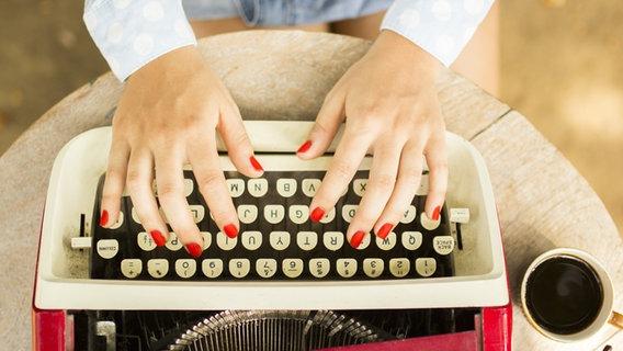 Zwei Hände mit roten Fingernägeln tippen auf einer alten Schreibmaschine. © Fotolia/peshkov