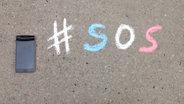 Der Hashtag SOS auf Beton geschrieben. © Pascal Strehler / N-JOY Foto: Pascal Strehler