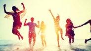 Junge Leute laufen und springen ausgelassen bei einem Sonnenuntergang am Strand aus dem Meer. © fotolia.com Fotograf: Rawpixel.com