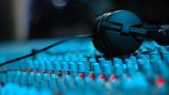 Kopfhörer liegen auf einem Mischpult. © fotolia Foto: Xandros