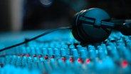 Kopfhörer liegen auf einem Mischpult. © fotolia Fotograf: Xandros