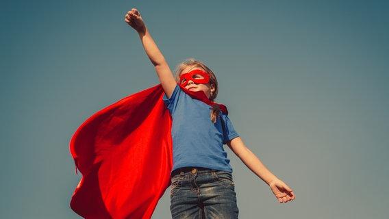 Ein Mädchen mit Superman-Kostüm und geballter Faust, in die Luft gestreckt. © Fotolia/yuryimaging