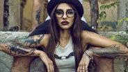 Eine junge tätowierte Frau mit Hut und Brille sitzt zwischen den Beinen eines Mannes. © Fotolia | Sobrik Foto: Fotolia | Sobrik