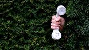 Ein Telefonhörer wird ins Bild gehalten. © Photocase Fotograf: Jonicore