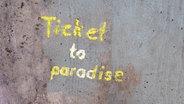 """Auf einer grauen Wand steht in gelber Schrift """"Ticket to paradise"""". © Photocase Foto: Knallgrün"""
