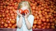 Ein Mädchen hält sich zwei Tomaten vor die Augen © imago/Westend61