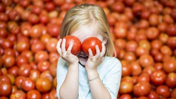 Ein Mädchen hält sich zwei Tomaten vor die Augen. © imago images/Westend61 Foto: Westend61