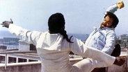 """Plattfuß (Bud Spencer, r.) holt zu einem Schlag gegen einen Rauschgifthändler aus im Film """"Sie nannten ihn Plattfuß"""". © imago/ United Archives"""