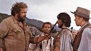 Bud Spencer (l.) steht neben Terence Hill in einem Western-Film und hält einem Gegner eine Pistole unter die Nase. © imago/ United Archives