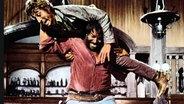 """Im Film """"Vier für ein Ave Maria"""" wirft Hutch (Bud Spencer) einen Gegner auf den Boden. © imago/ United Archives"""