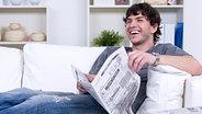 Junger Mann hält eine Zeitung in den Händen und lacht © Fotolia.com Fotograf: Valua Vitaly